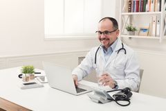 Portrait of doctor in glasses sitting at desktop stock photo