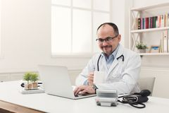Portrait of doctor in glasses sitting at desktop royalty free stock photo
