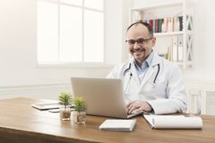 Portrait of doctor in glasses sitting at desktop stock photography
