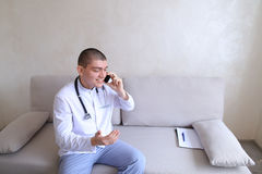 Portrait of doctor guy who on mobile gives advice to patients si stock images