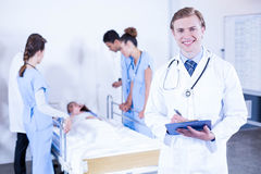 Portrait of doctor holding clipboard. And other doctor examining a patient behind Stock Photography