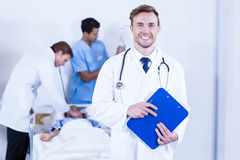 Portrait of doctor holding clipboard. And other doctor examining a patient behind in hospital Royalty Free Stock Photos