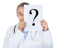 Portrait of doctor holding paper with question mark Stock Image