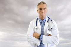 Portrait of doctor in lab coat with overcast sky in background Stock Photography