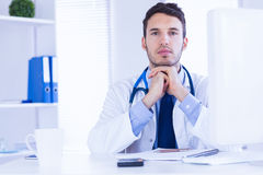 Portrait of doctor looking at camera with hands folded Royalty Free Stock Images