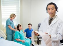 Portrait of Doctor in Maternity Ward. Portrait of mature male doctor holding fetal monitorreport with nurse, husband and pregnant wife in background Stock Photo