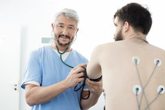 Portrait Of Doctor Measuring Blood Pressure Of Patient In Hospit Stock Photos