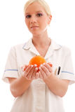 Portrait of a doctor or nurse holding fruit. Against white background royalty free stock image