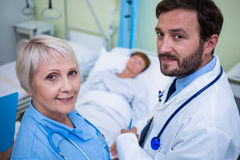 Portrait of doctor and nurse standing in hospital room Royalty Free Stock Photo