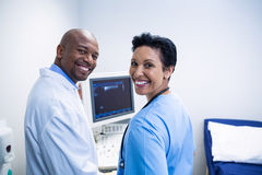 Portrait of doctor and nurse standing near patient monitoring machine Royalty Free Stock Photography