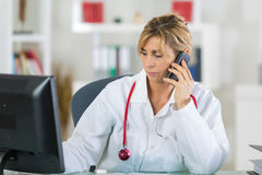 Portrait doctor in office using smartphone Royalty Free Stock Photography