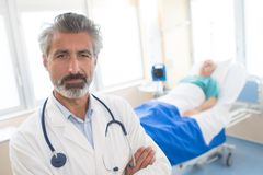 Portrait doctor with patient in bed in background. Portrait of doctor with patient in bed in background Royalty Free Stock Photos