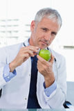 Portrait of a doctor putting his stethoscope on an apple Stock Photos
