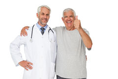 Portrait of a doctor with senior man gesturing thumbs up Royalty Free Stock Photos