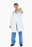 Portrait of a doctor showing an apple. Against a white background Royalty Free Stock Images