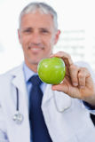 Portrait of a doctor showing an apple. In his office Royalty Free Stock Photos