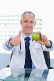 Portrait of a doctor showing an apple with the thumb up. In his office Royalty Free Stock Images