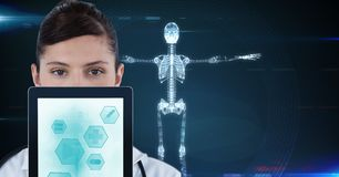 Portrait of doctor showing medical icons on tablet PC with skeleton in background Stock Images