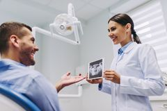 Doctor showing x-ray to the patient royalty free stock photos