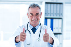 Portrait of doctor showing thumps up sign in clinic Stock Photography