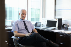 Portrait Of Doctor Sitting At Desk In Office Stock Image