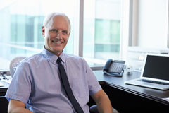 Portrait Of Doctor Sitting At Desk In Office Royalty Free Stock Photo