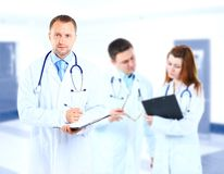 Portrait doctor smiling with colleagues. In background Royalty Free Stock Images