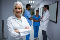 Portrait of doctor standing with arms crossed in corridor Stock Images