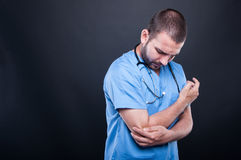 Portrait of doctor wearing scrubs having elbow pain Royalty Free Stock Image