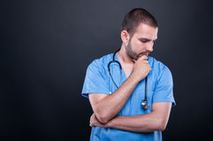 Portrait of doctor wearing scrubs with stethoscope thinking. Looking down on black background with copypsace advertising area stock images