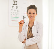 Portrait of doctor woman with eyeglasses. In front of snellen chart Stock Photography