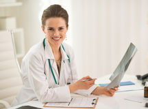 Portrait of doctor woman holding fluorography. Portrait of happy doctor woman holding fluorography in office Royalty Free Stock Image