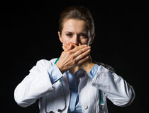 Portrait of doctor woman showing speak no evil gesture. Isolated on black Stock Images