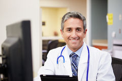 Portrait Of Doctor Working At Nurses Station Stock Photos