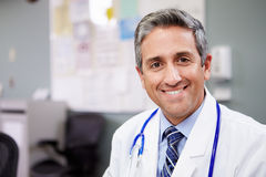 Portrait Of Doctor Working At Nurses Station. Smiling At Camera royalty free stock image