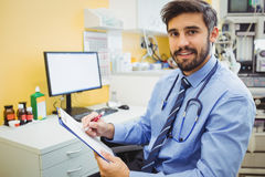 Portrait of doctor writing on a clipboard. At the hospital Royalty Free Stock Photos