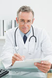 Portrait of a doctor writing a report at office Royalty Free Stock Photos