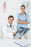 Portrait of doctors examining xray in medical office Royalty Free Stock Images