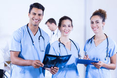 Portrait of doctors holding a x- ray and smiling Stock Photography