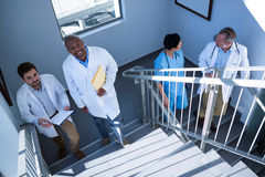 Portrait of doctors interacting with each other while climbing stairs Stock Photography