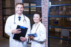 Portrait of doctors standing near library with clipboard and digital tablet Stock Image