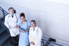 Portrait of doctors standing on staircase with document Royalty Free Stock Photos