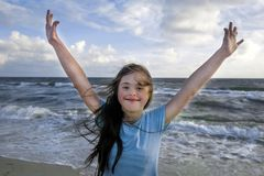 Portrait of down syndrome girl smiling on background of the seaÑŽ. Portrait of down syndrome girl smiling on background of the sea stock images