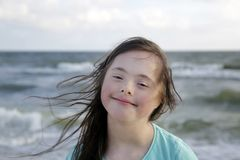 Portrait of down syndrome girl smiling on background of the sea royalty free stock photography