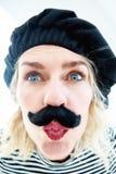 Portrait drôle de femme blonde en tant qu'homme français avec le béret et le musta Photographie stock libre de droits
