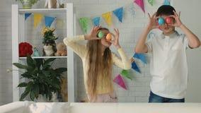 Portrait drôle de garçon heureux et de fille jouant avec des oeufs de pâques banque de vidéos