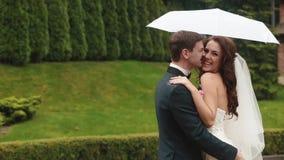 Portrait drôle des jeunes couples de sourire attrayants se tenant sous le parapluie sous la pluie Le marié mord doucement banque de vidéos