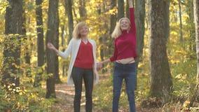 Portrait drôle extérieur des filles en automne Filles de beauté ayant l'amusement dans le parc d'automne Danse drôle d'automne, d banque de vidéos
