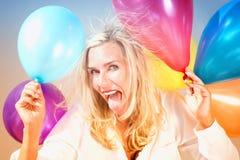 Portrait drôle de femme blonde avec des ballons photographie stock libre de droits