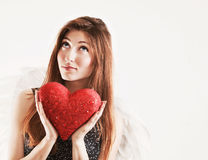 Portrait of dreaming girl as angel with red heart Stock Images